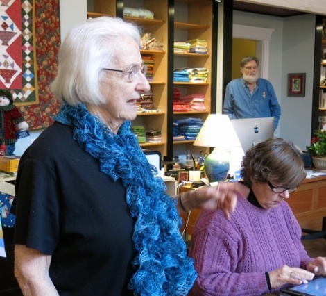 Pat with her hand made scarf. Anne typing in notes and Jim observing it all!